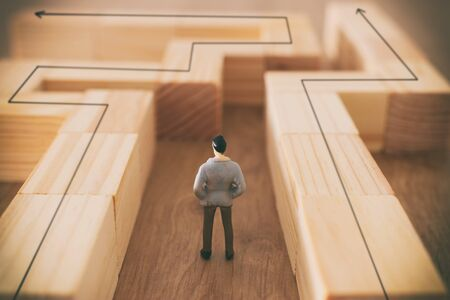 business concept image of and challenge. A man stands in the maze looking for the exit. Problem solving and decision making idea
