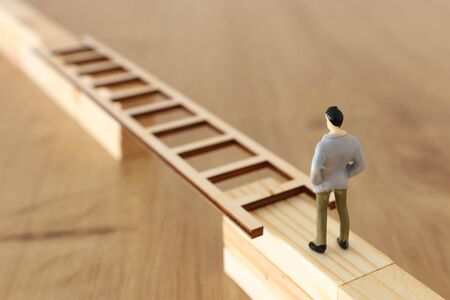 business concept picture of challenge. A man stands on the edge of a high wall and passes the gap by placing a ladder. Problem solving and decisionmaking. Banque d'images