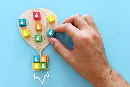 Immagine aziendale di mongolfiera in legno con icone di persone su tavolo blu, risorse umane e concetto di gestione