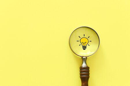 Immagine di concetto di affari. Lente d'ingrandimento e lampada. Trovare l'idea e l'ispirazione migliori tra le altre