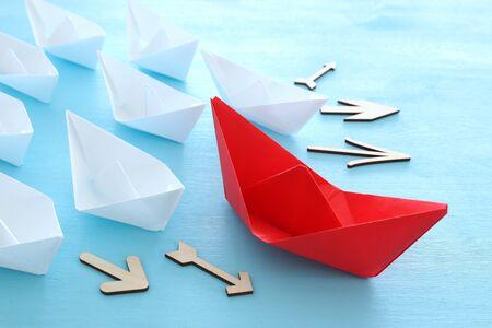 negocio. Imagen del concepto de liderazgo con barcos de papel sobre fondo de madera azul. Un líder guiando a otros.