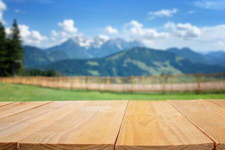 Tavolo vuoto davanti alla natura sfocata e allo sfondo delle montagne. Pronto per il montaggio del display del prodotto