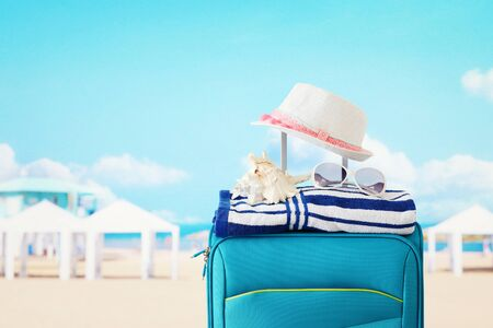 holidays. travel concept. blue suitcase with female hat, sea shell, sunglasses and beach towel in front of tropical background