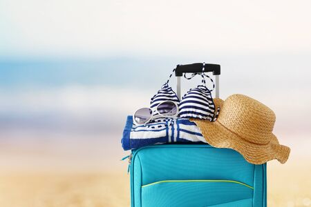 holidays. travel concept. blue suitcase with female hat, sunglasses bikini and beach towel in front of tropical background