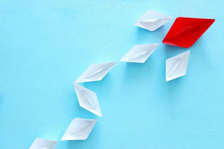 business. Leadership concept image with paper boats on blue wooden background. One leader guiding others. 版權商用圖片