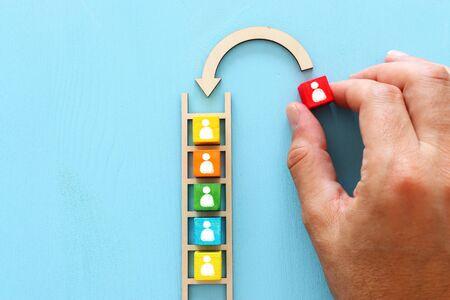 Image d'entreprise d'une échelle en bois avec des icônes de personnes sur une table bleue, des ressources humaines et un concept de gestion Banque d'images