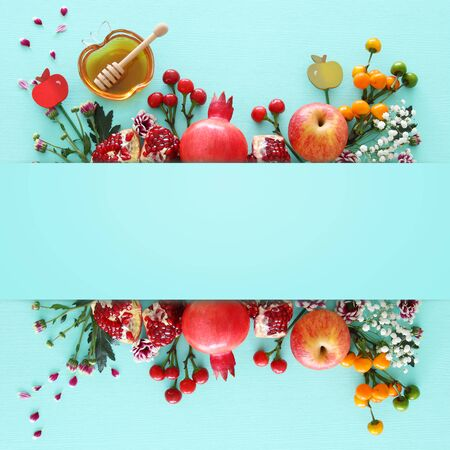 Religion image of Rosh hashanah (Jewish New Year holiday) concept. Traditional symbols over wooden mint blue pastel background
