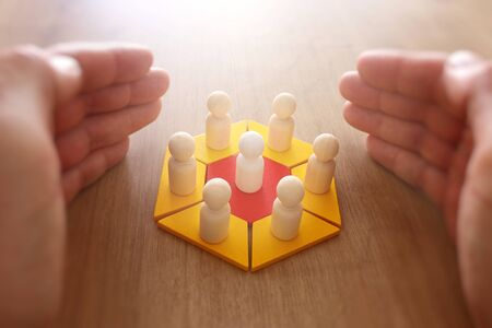 business concept image of tangram puzzle blocks with people figures over wooden table ,human resources and management concept