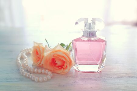 beauty/fashion Image of elegant perfume bottle, white pearls and delicate roses over pastel background. vintage filtered image