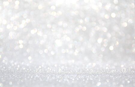 background of abstract glitter lights. silver and white. de-focused