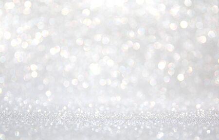 Fondo de luces de brillo abstracto. plateado y blanco. desenfocado