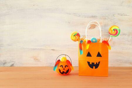 imagen de vacaciones de Halloween. Calabazas y bolsa de regalo de papel sobre mesa de madera Foto de archivo