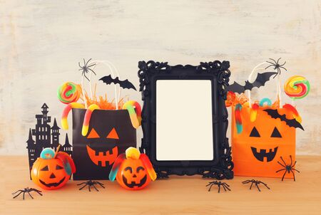 holidays image of Halloween. Pumpkins, bats, treats, paper gift bag next to empty photo frame for mockup over wooden table. for photography montage