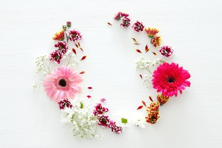 spring bouquet of pink, yellow, orange and purple flowers over white wooden background. top view, flat lay