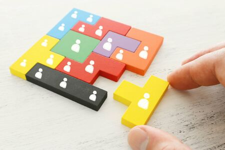 business concept image of tangram puzzle blocks with people icons over wooden table ,human resources and management concept Stockfoto
