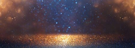 blackground of abstract glitter lights. blue, gold and black. de focused. banner