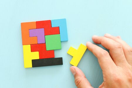 business concept image of a colorful square tangram puzzle, over wooden table