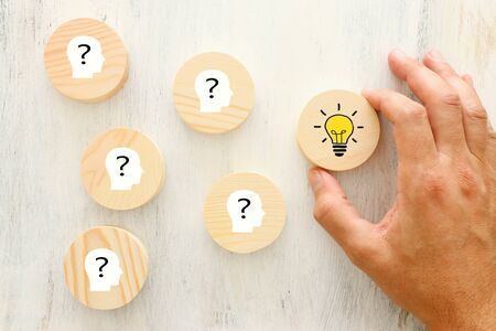 Business Concept image of revealing an idea, finding the right solution during creative process. Hand picking round cube with bright light bulb Imagens - 128866663