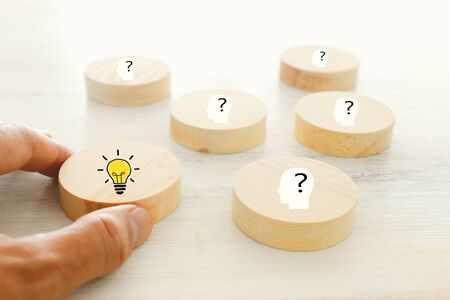 Business Concept image of revealing an idea, finding the right solution during creative process. Hand picking round cube with bright light bulb