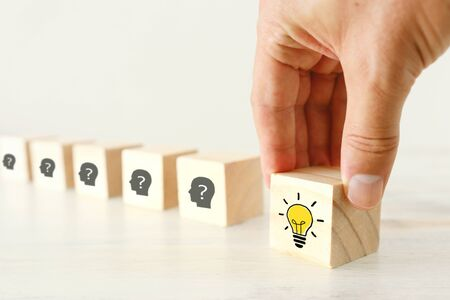 Business Concept image of revealing an idea, finding the right solution during creative process. Hand picking cube with bright light bulb