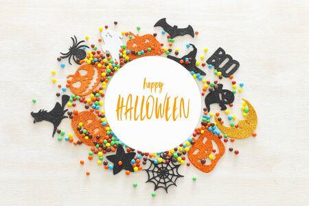 Feiertagsbild von Halloween. Kürbisse, Fledermäuse, Leckereien, Fledermaus und Hexe auf weißem Hintergrund aus Holz. Ansicht von oben, flach