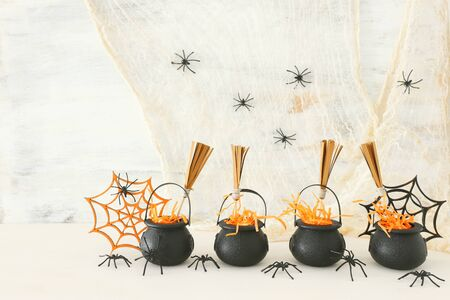 holidays image of Halloween. Witcher cauldron, broom and spiders over white wooden table Foto de archivo
