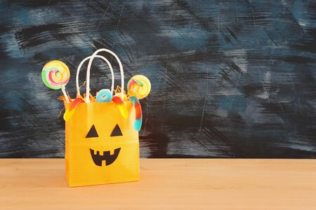 holidays image of Halloween. paper gift bag over wooden table