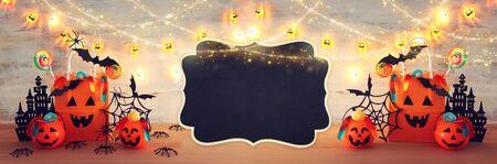 imagen de vacaciones de Halloween. Calabazas, murciélagos, golosinas, bolsa de regalo de papel sobre mesa de madera Foto de archivo