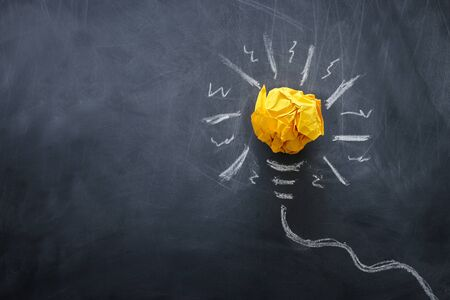 Education concept image. Creative idea and innovation. Crumpled paper as lightbulb metaphor over blackboard Stok Fotoğraf