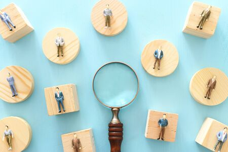 Business image of magnifying glass with people figures over blue background, building a strong team, human resources and management concept