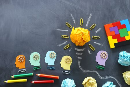 Education concept image. Creative idea and innovation. Crumpled paper as lightbulb metaphor over blackboard