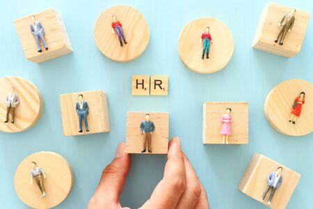 Business image of miniature people over blue table, human resources and management concept