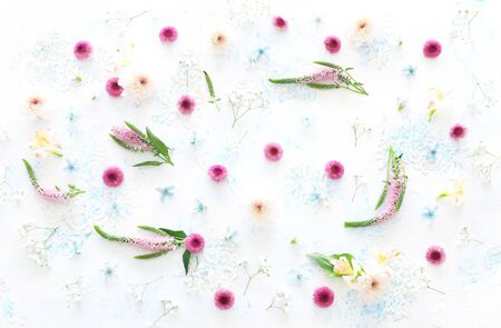 nature image of spring pastel of pink, white and light blue flowers over delicate wooden background. top view, flat lay