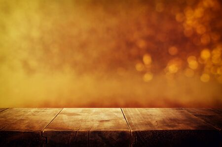 background of wooden table in front of glitter gold bokeh lights. For product presentation