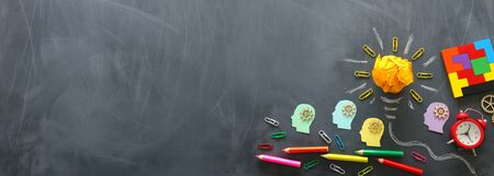 Onderwijs concept afbeelding. Creatief idee en innovatie. Verfrommeld papier als gloeilamp metafoor over schoolbord Stockfoto