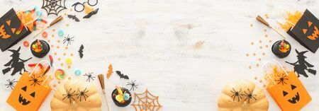 holidays image of Halloween. Pumpkins, bats, treats and cute witch over white wooden background. top view, flat lay. banner Archivio Fotografico