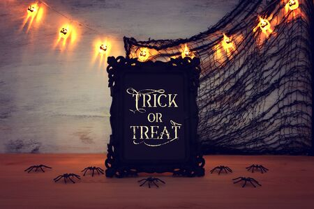 holidays image of Halloween. photo frame with text over wooden table