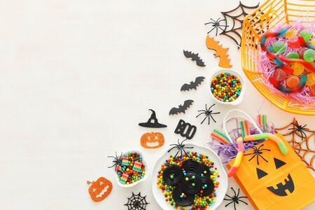 holidays image of Halloween. Pumpkins, bats, treats over white wooden background. top view, flat lay