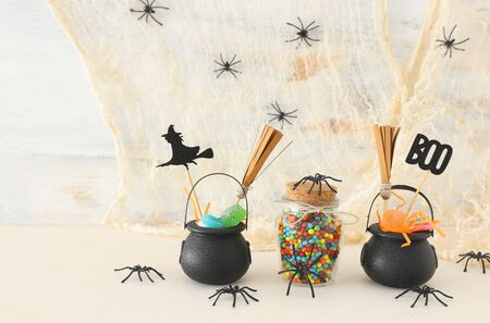 holidays image of Halloween. Witcher cauldron, broom, candies and spiders over white wooden table