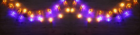 holidays concept of Halloween background with colorful garland lights Фото со стока