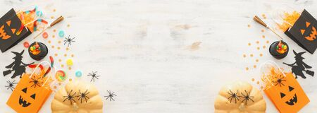 holidays image of Halloween. Pumpkins, bats, treats and cute witch over white wooden background. top view, flat lay. banner Фото со стока