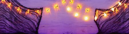 holidays concept of Halloween background with spider web and colorful garland lights Фото со стока