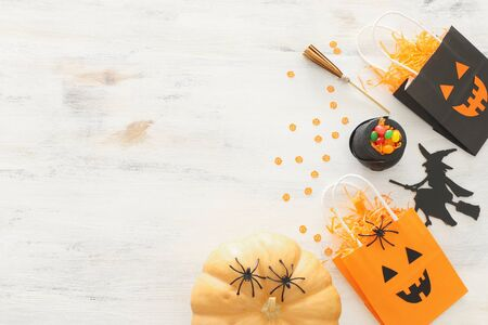holidays image of Halloween. Pumpkins, bats, treats and cute witch over white wooden background. top view, flat lay