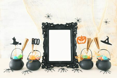 holidays image of Halloween. Witcher cauldron, broom, candies and spiders next to empty photo frame for mockup over wooden table. for photography montage