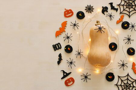 holidays Halloween image. pumpkin and gold garlan lights over wooden white table. top view, flat lay Фото со стока