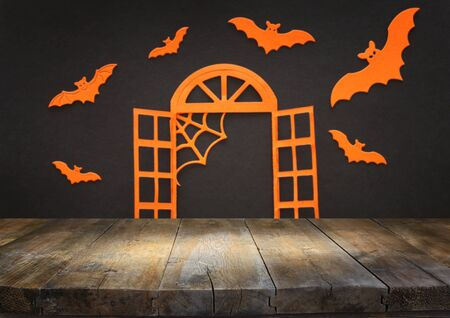 holidays concept of Halloween. Empty rustic table in front of open window and bats over black background. Ready for product display montage