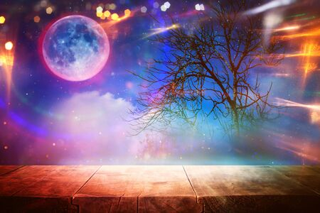 Holidays Halloween concept. Empty rustic table in front of scary and misty night sky and full moon background. Ready for product display montage