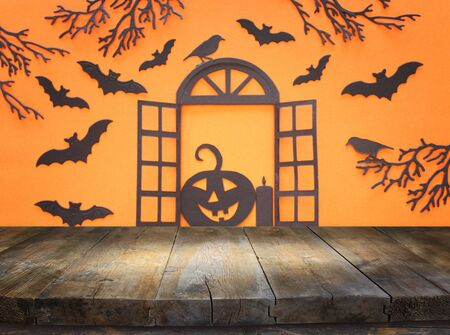 holidays concept of Halloween. Empty rustic table in front of open window and bats over orangr background. Ready for product display montage