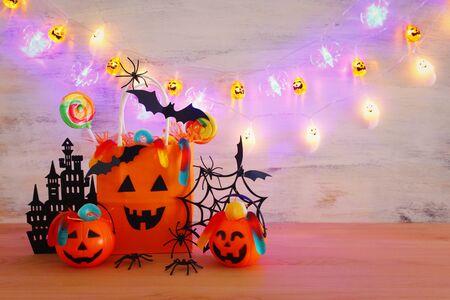 holidays image of Halloween. Pumpkins, bats, treats, paper gift bag over wooden table