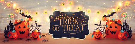 imagen de vacaciones de Halloween. Calabazas, murciélagos, golosinas, bolsa de regalo de papel sobre mesa de madera